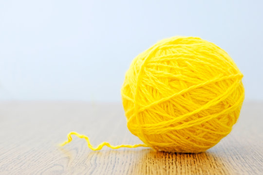 Yellow ball of thread on a light background. Craft or knitting concept. The idea of solving the case.