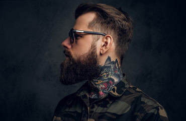 Profile of a stylish bearded guy with tattooed hands in the military shirt. Studio photo against dark wall