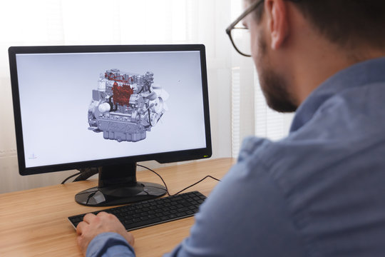 Engineer, Constructor, Designer in Glasses Working on a Personal Computer. He is Creating, Designing a New 3D Model of Car Engine, Motor in CAD Program. Freelance Work