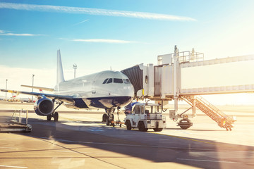 Big modern commercial plane on airfield docked with boarding bridge at sunrise or sunset. Blue clear sky on background. Travel and tourist destination concept Wall mural