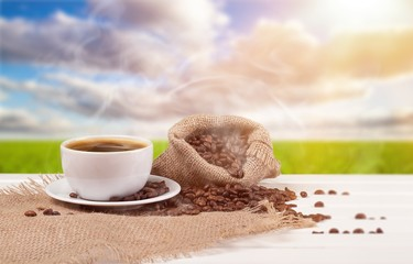 Cup of hot coffee with beans on background