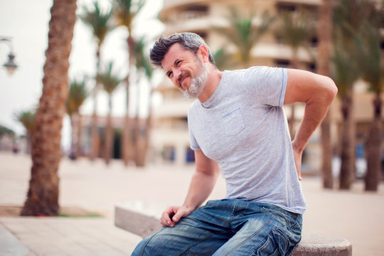 Man with back pain sitting on bench at the outdoor. People, health care and medicine concept