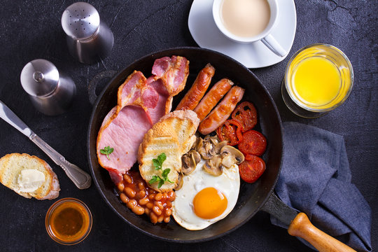 Full English or Irish breakfast with sausages, bacon, eggs, tomatoes, mushrooms and beans on black background