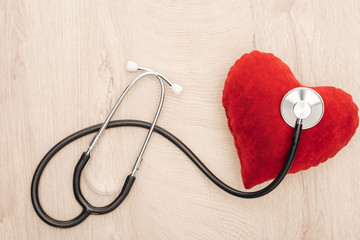 top view of stethoscope and toy heart on wooden background