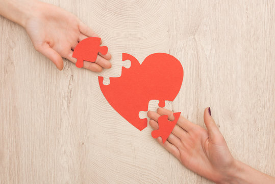 cropped view of women holding pieces of puzzle and paper heart