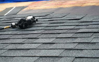 close up on nail gun on the roof shingle