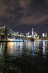 Blurred view of Financial District at night from East River
