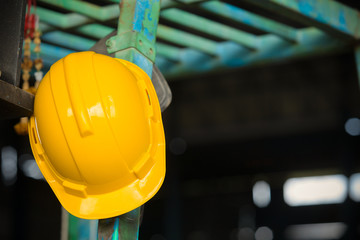 Safety helmet hat hung on construction site,Yellow helmet hung on construction site,Work safety at construction site concept . Wall mural