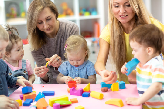 Kindergarten kids play at with teacher and educator