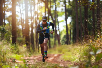 Fototapeta A man Runner of Trail . and athlete's feet wearing sports shoes for trail running in the forest obraz