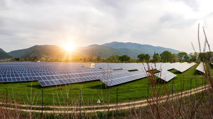 Panoramic view of solar panels, photovoltaics, alternative electricity source. View of a solar station at the foothills of a mountain - concept of sustainable resources