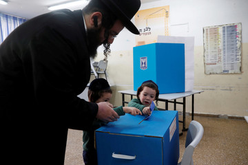 An ultra-Orthodox Jewish man helps kids cast his ballot at a polling station as Israelis vote in a parliamentary election, in Jerusalem