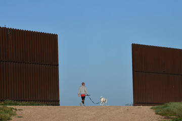 A man walks his dog past a stretch of border fence in the Rio Grande Valley near Penitas