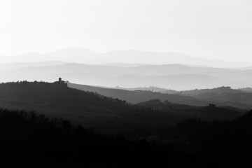 Beautiful view of Tuscany hills at sunset with mist