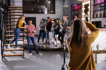 Woman taking photo of young coworkers during coffee break in cafe
