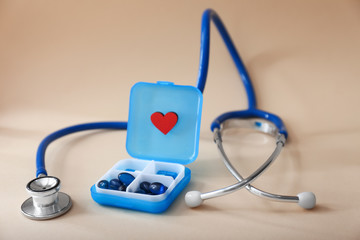 Stethoscope with pills on color background