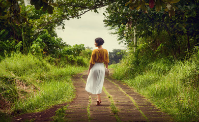 A girl in a dress walks along the path of the artist. Travel to Bali. Campuhan Ridge Walk. Wall mural