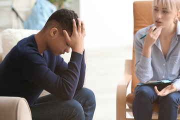 Female psychologist working with depressed teenage boy in office