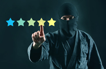 Mystery shopper or review online concept. Rating online. 5 stars review and ninja in mask on a dark background.