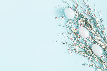 Easter composition. Easter eggs, white flowers on pastel blue background. Flat lay, top view, copy...