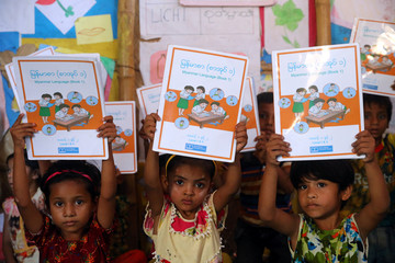 Rohingya refugee children show their Myanmar language books as they pose for a picture during a class at a refugee camp in Cox's Bazar