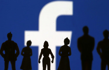 Small toy figures are seen in front of Facebook logo in this illustration picture