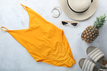 Female swimming suit, hat, pineapple and beach shoes on light background. Travel concept