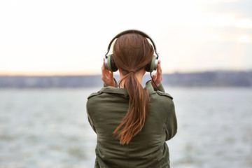 Young woman listening to music near river
