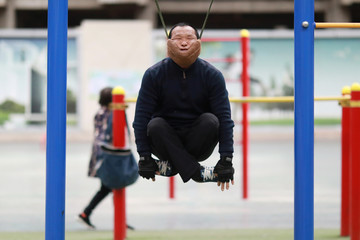Sun Rongchun exercises with an improvised cervical traction device attached to a high bar at a sports complex in Shenyang