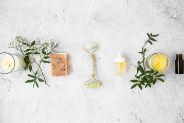 Natural organic skincare products on concrete background, top view, green natural skincare and beauty care with natural soap,jade roller, essential oils bottles, floral extracts and candle Fotoväggar