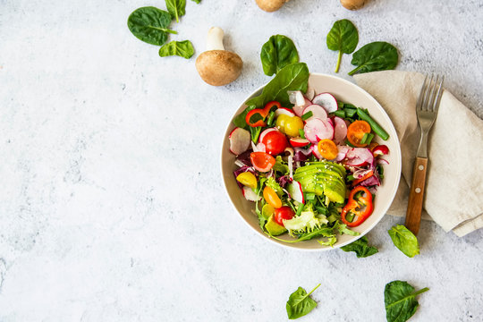 Healthy salad with bio organic vegetables, green vegan meal with avocado, pepper, radish, tomatoes, lettuce, cabbage, spring colorful salad closeup, clean eating concept top view