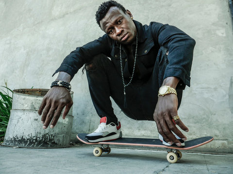 young attractive and serious black African American man squatting on skate board at grunge street corner looking cool posing in badass bad boy attitude in city life