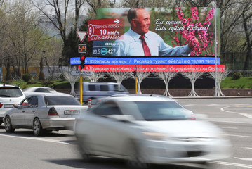 Cars drive past a screen showing an image of Kazakh former President Nazarbayev in central Almaty
