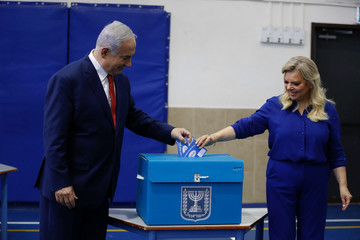 Israel's Prime Minister Benjamin Netanyahu casts his vote with his wife Sara during Israel's parliamentary election in Jerusalem