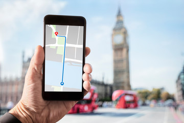 Hand holding smartphone with map on screen in London