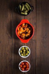 Four tapas dishes in a vertical column on a wooden table