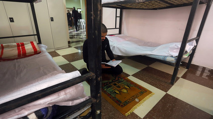 An Iraqi suspect who was arrested for drug-related crimes prays inside a rehab center in Basra