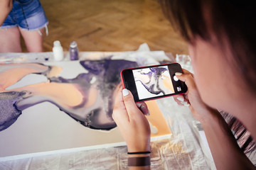 Pupils photograph a picture of an artist's teacher during a master class on a smartphone. The concept of a talented artist, workshop
