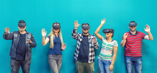 Group of friends using new technology playing on vr glasses indoor – virtual reality with people having fun together