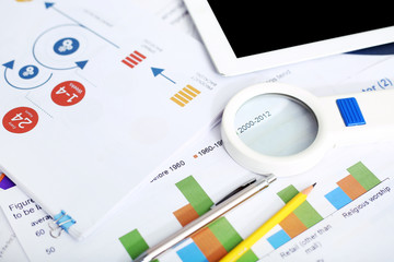 Picture of financial paper, tablet, magnifying glass, pencil and pen.