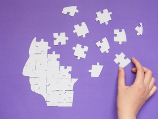 Female hand trying to connect pieces of white jigsaw puzzle as a human head brain on purple background. Creative idea for solving problem, memory loss, mental health or psychosis treatment concept. Wall mural
