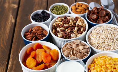 various cereals, nuts and dried fruits on wooden surface
