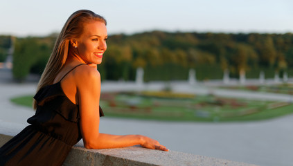 Happy young positive woman posing in park at sunset