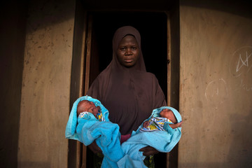 A Muslim woman carries her four-day-old male twins wrapped in blue towels outside the door of her home in Igbo Ora