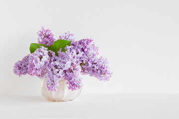 Fresh branches of purple lilac blossoms in vase on table at light gray wall. Empty place for inspirational, emotional, sentimental text, quote or sayings. Front view.