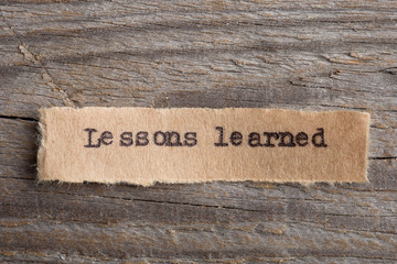 lessons learned - word on a piece of paper close up, business creative motivation concept