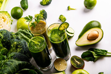 Different healthy vegan spinach, kiwi and cucumber drinks on the white wooden background. Raw drinks and foods. Flat lay.