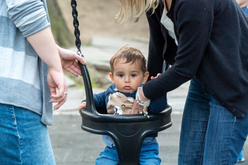 Putting small child in a swing