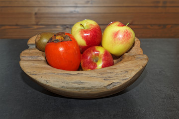 Scene of fruits in a wooden bowl on dark table