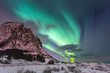 Northern lights at night against the backdrop of beautiful mountains and green sky